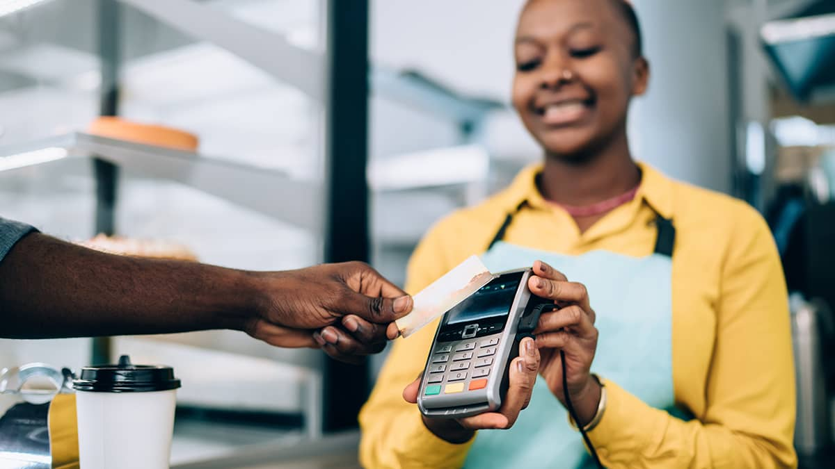 saleswoman holding credit card machine as customer pays a price based on markup percentage