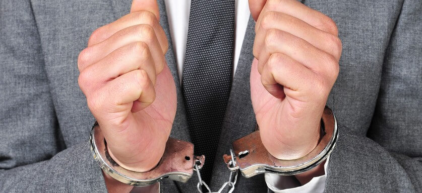 payroll fraud cases - how small businesses can fight payroll fraud man in handcuffs