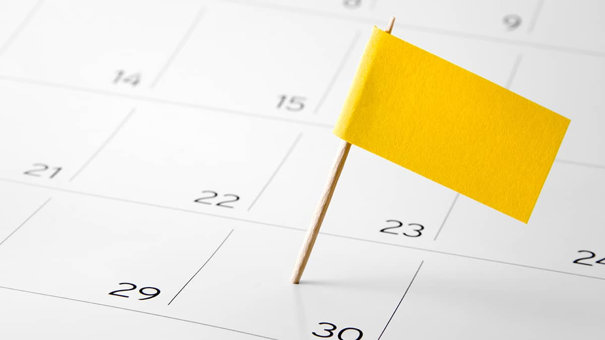 yellow flag marking specific date on a desk calendar