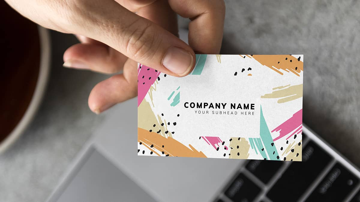 hand holding colorful business card out