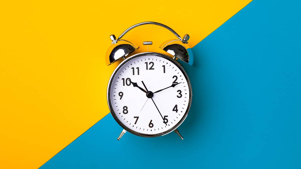 clock ticking with a bright yellow and blue background