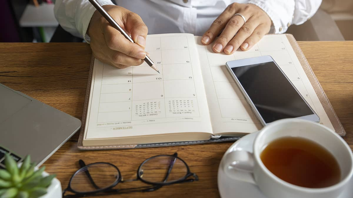 desk with a calendar, cell phone, glasses, and a cup of tea