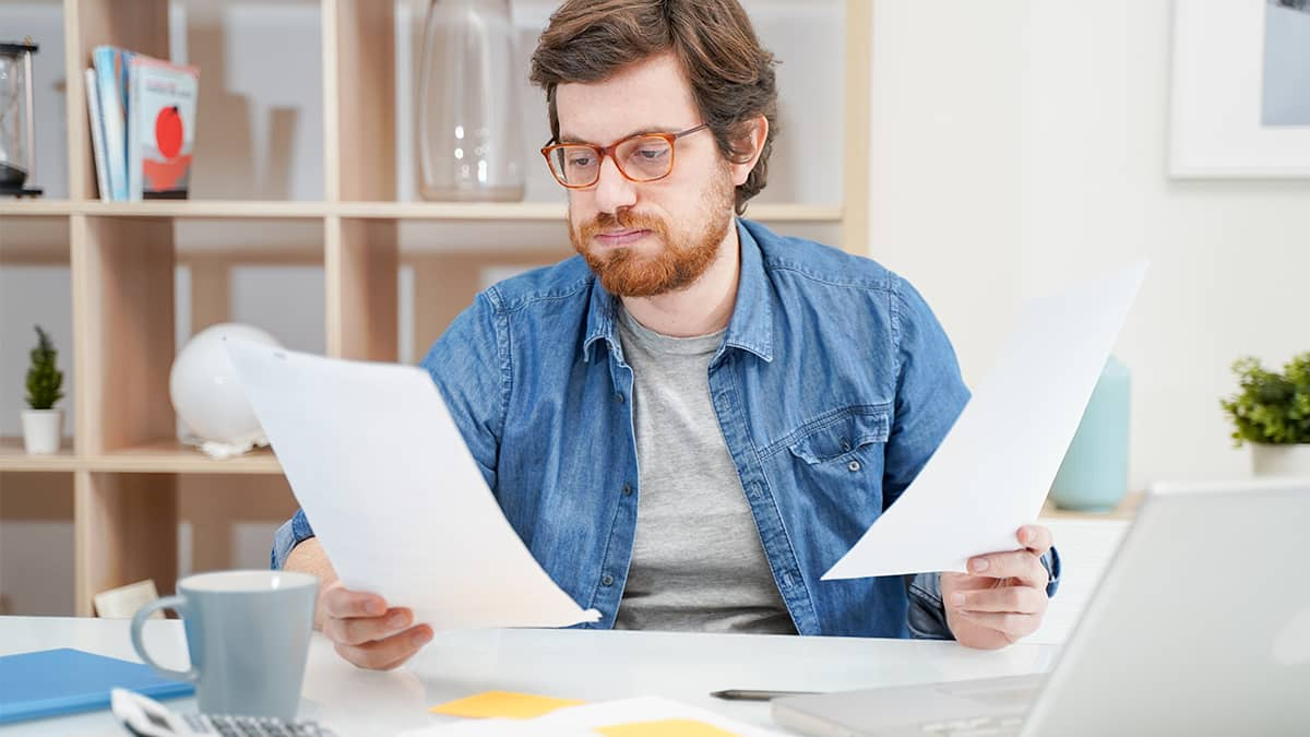 man deciding how to calculate a raise by looking at papers