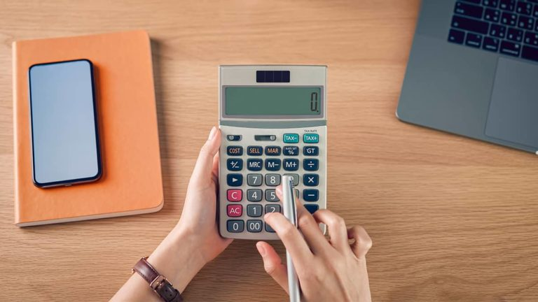 business owner using a calculator and income tax withholding tables to determine federal income tax withholding