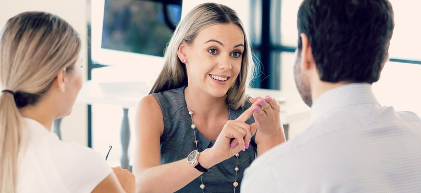 woman providing instructions on creating overtime policy to two workers