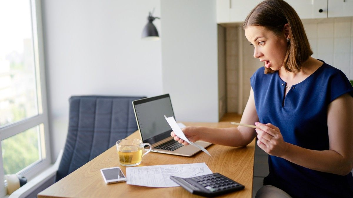 Surprised woman using a laptop computer sitting at her kitchen holding bank statements