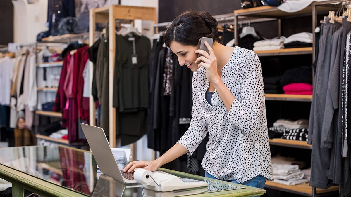 woman on phone using laptop in a clothing store, creating a sales journal entry