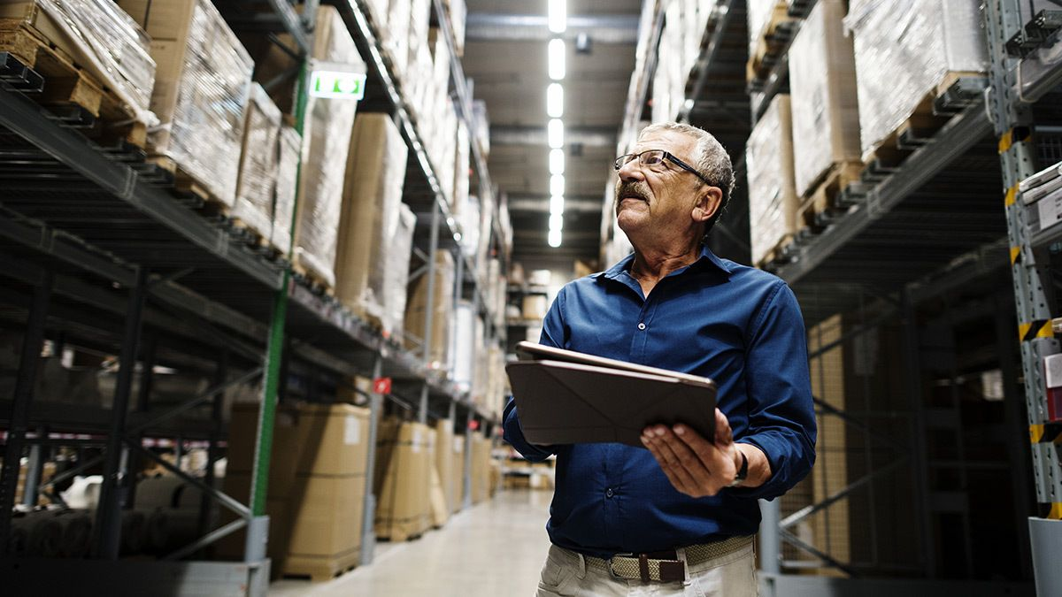 man reviewing inventory levels in a warehouse