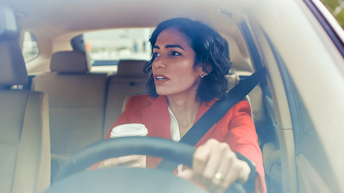 woman in orange blazer driving and holding a cup of coffee while looking in the rearview mirror