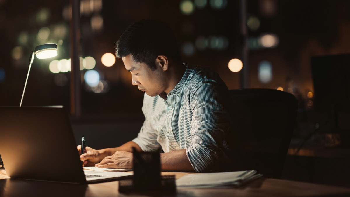 man working late at night with lamp light