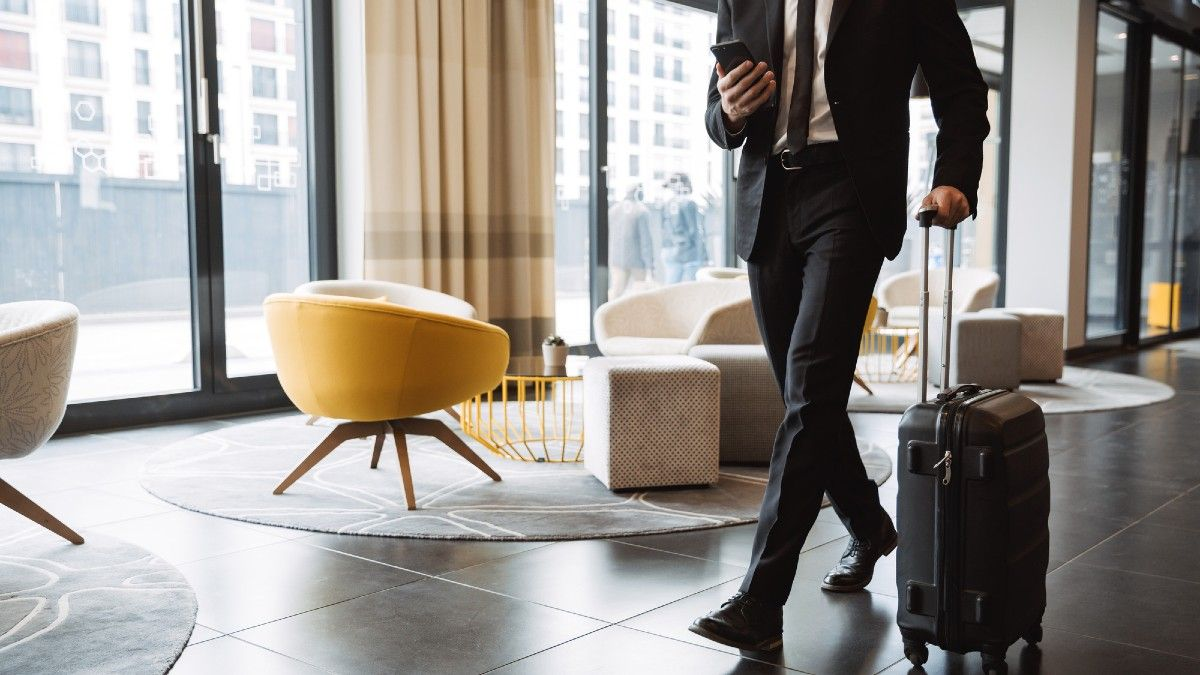 businessman wearing formal black suit holding smartphone and walking with suitcase in hotel lobby