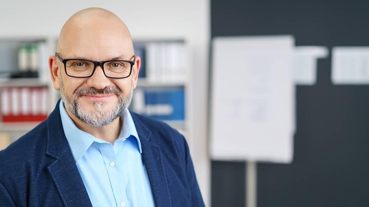 man wearing glasses smiling at the camera